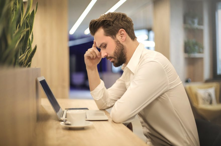 man thinking why outsource his business tasks while looking at laptop