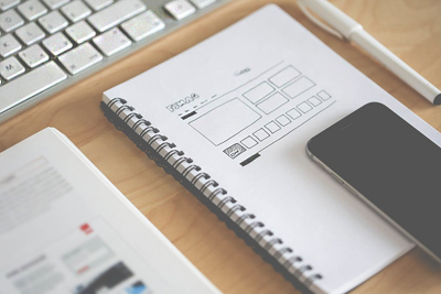 A Notebook, and a Smartphone used for outsourcing web design