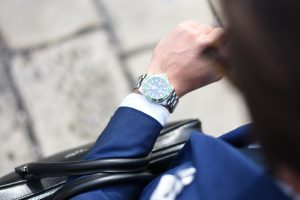 effective time management - a man in blue suit looking in a wrist watch
