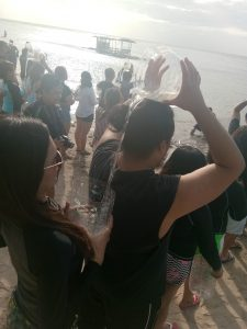 A player pours water into another player in the Water Relay Game