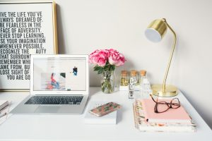 a cute office table with a laptop and papers in its side and following a list of desktop must-haves