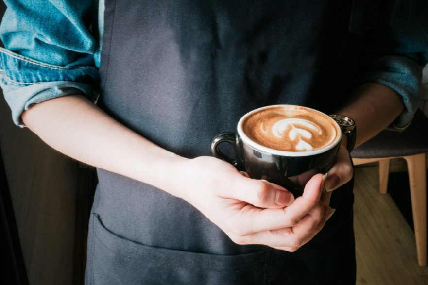 Barista holding coffee cup in a cafe