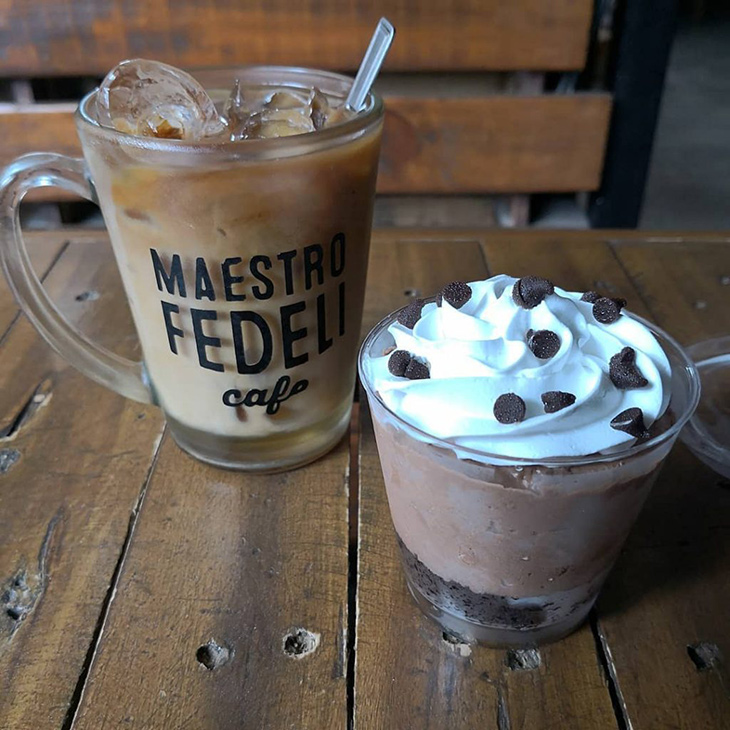 Iced coffee in a transparent mug with Maestro Fedeli cafe print and chocolate desert with whipped cream and chocolate chip