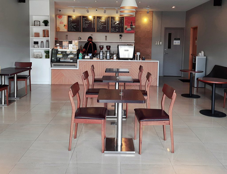 Coffee shop with chairs and tables and barista in the coffee counter