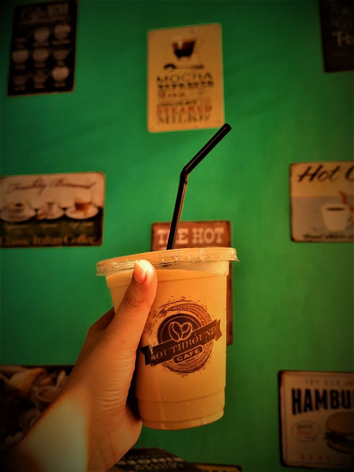 someone holding an 8oz-size Iced coffee on a green wall background