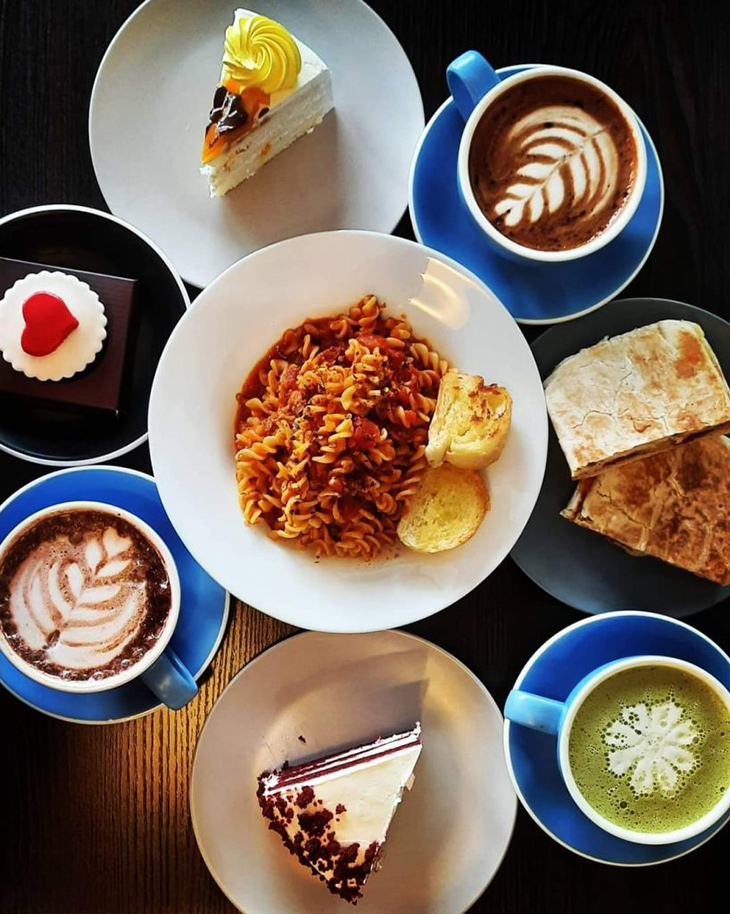 Flat lay of food and drinks. Pasta in the center with three drinks and slices of cakes on its side