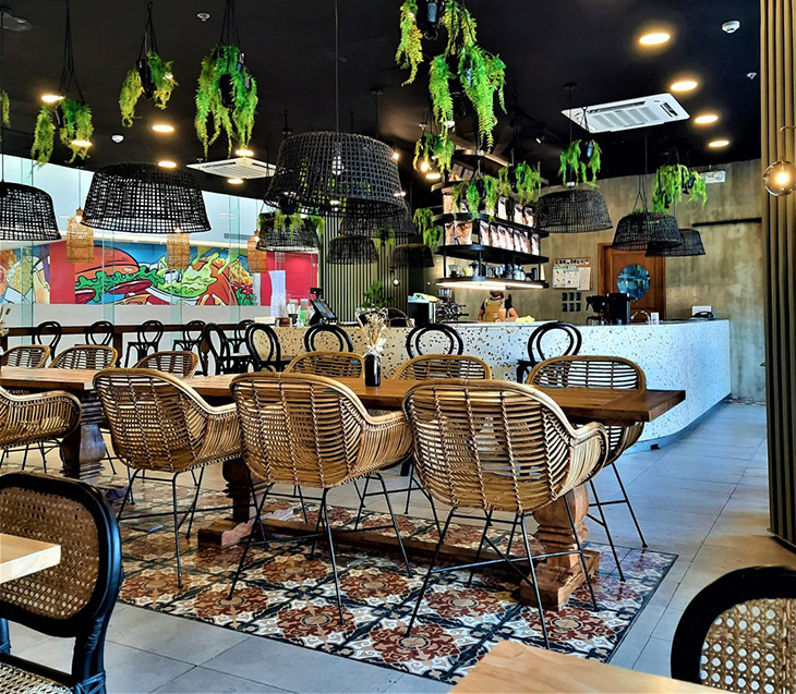 Coffee shop with chairs and pendant lighting made of rattan, wooden tables, and hanging plants