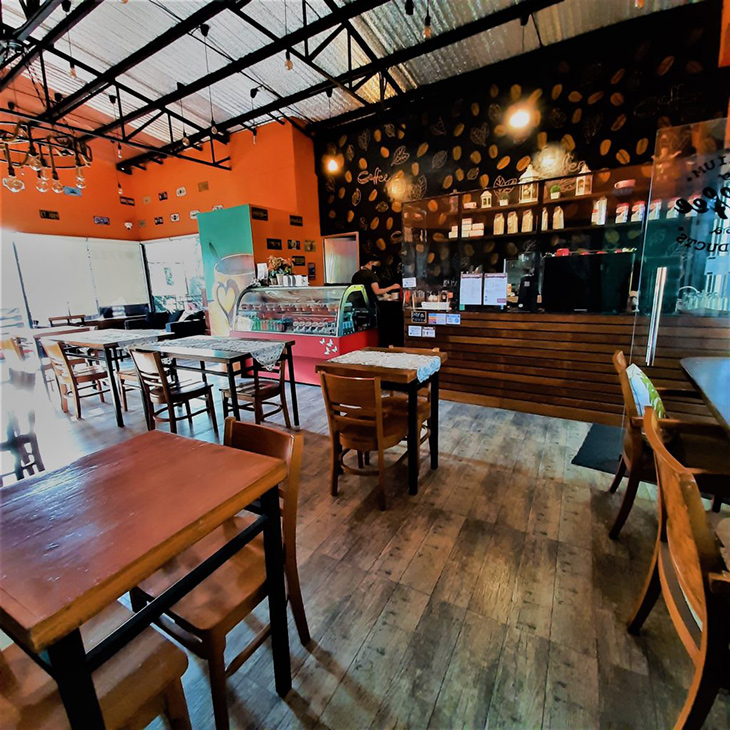 A coffee shop with wooden chairs and tables, orange walls, and coffee bean wallpaper on the coffee counter